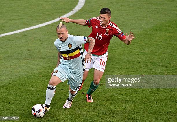 Belgium's midfielder Radja Nainggolan is marked by Hungary's midfielder Adam Pinter during the Euro 2016 round of 16 football match between Hungary...