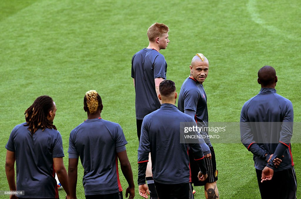 Belgium's midfielders Kevin De Bruyne (top) and Radja Nainggolan (2nd R) arrive with teammates for a training session at the Stade de Lyon on June 12, 2016 on the eve of their opening match against Italy for the EURO 2016 football tournamnet. / AFP / VINCENZO