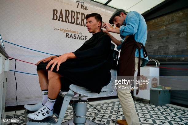 Belgium's Oliver Naesen gets his hair cut at the departure village prior to the 2075 km fourth stage of the 104th edition of the Tour de France...