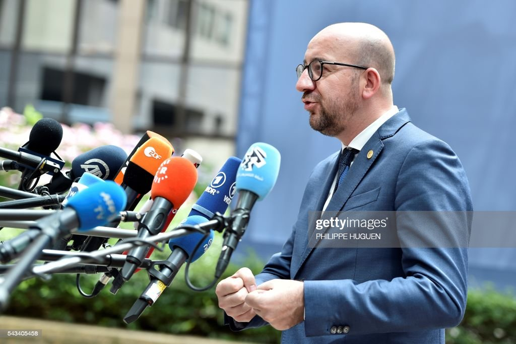 Belgium's Prime minister Charles Michel talks to journalists as he arrives before an EU summit meeting on June 28, 2016 at the European Union headquarters in Brussels. / AFP / PHILIPPE