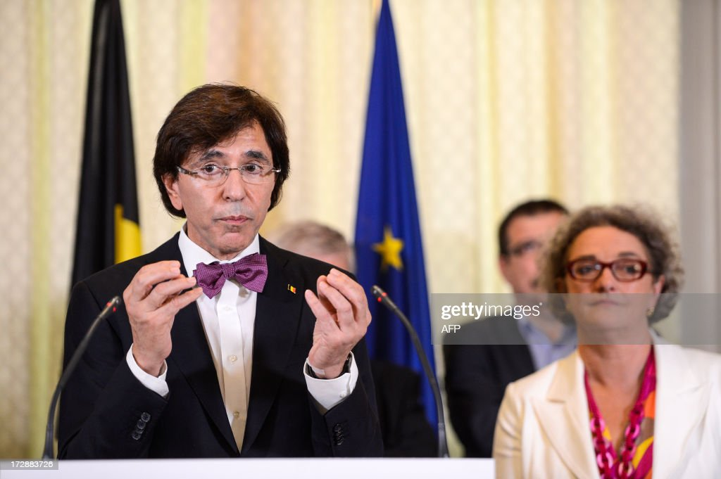 Belgium's Prime Minister Elio Di Rupo (L) delivers a speech near Belgian Minister of Employment Monica De Coninck (sp.a Flemish Socialists) (back R) during a press conference on July 5, 2013, in Brussels, following a meeting between trade union representatives and employer organisations at the cabinet of federal Employment Ministry, to discuss the harmonisation of the statutes of workers and employees. AFP PHOTO / BELGA / LAURIE DIEFFEMBACQBelgium Out