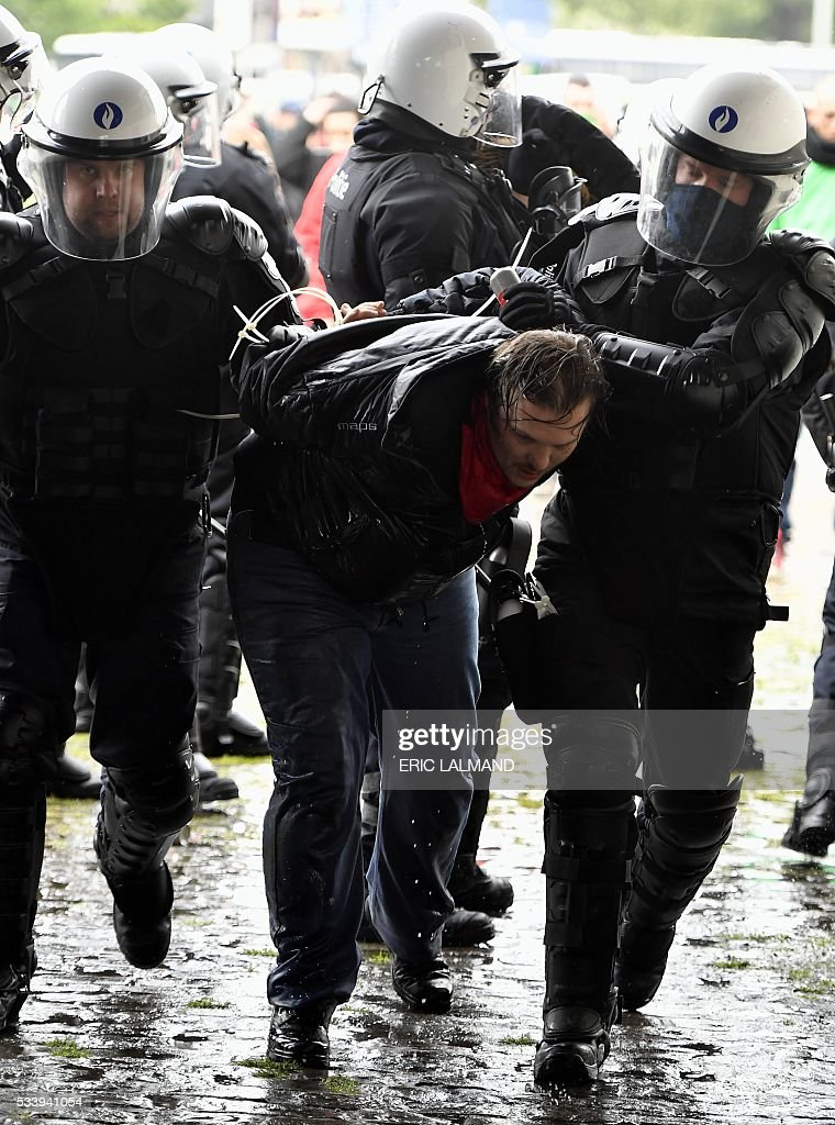 Belgium's riot police arrest a demonstrator during a national anti-austerity demonstration on May 24, 2016, in Brussels. Belgian trade unions called for mass protests against the centre-right government's proposed work reforms as they plan rallies and strikes over the next few months. / AFP / BELGA / ERIC LALMAND / Belgium OUT