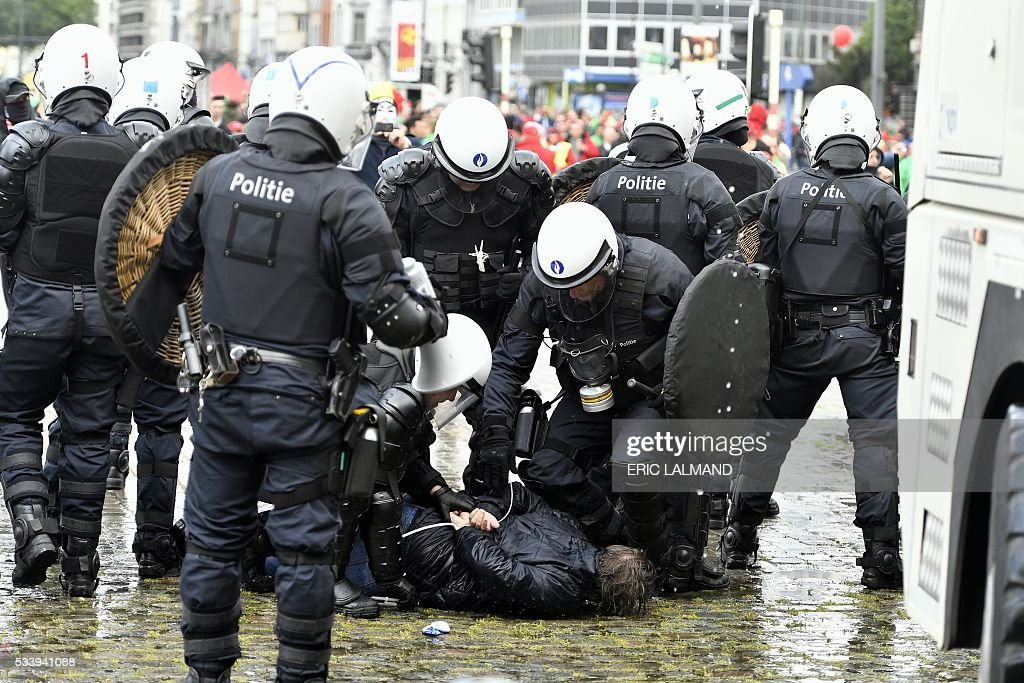TOPSHOT - Belgium's riot police arrest a demonstrator during a national anti-austerity demonstration on May 24, 2016, in Brussels. Belgian trade unions called for mass protests against the centre-right government's proposed work reforms as they plan rallies and strikes over the next few months. / AFP / BELGA / ERIC LALMAND / Belgium OUT