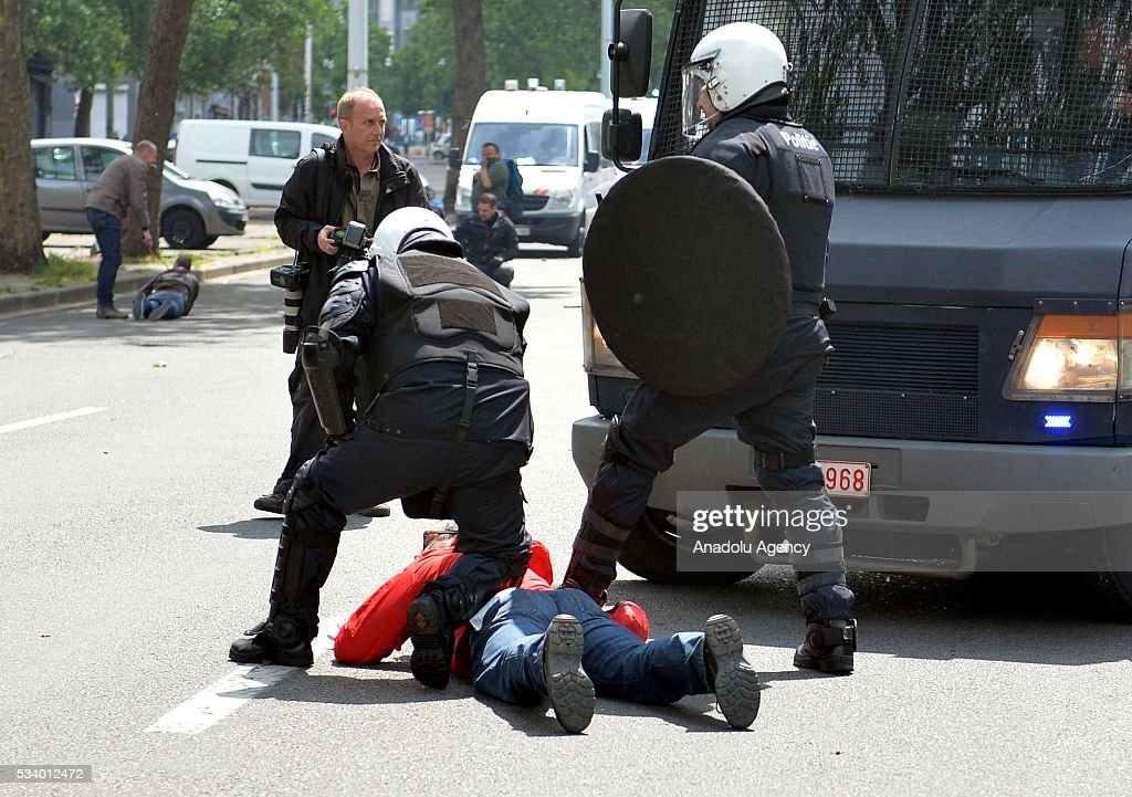 Belgium's riot police arrest a demonstrator during a national anti-austerity demonstration on May 24, 2016, in Brussels, Belgium. Belgian trade unions called for mass protest against the center-right government's social and economic policies.