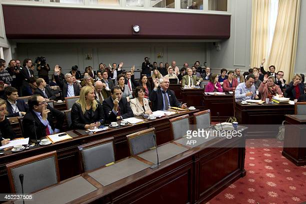 Belgium's Senate members vote during a session of the Senate's justice and social affairs commission on the expansion of the euthanasia law for...