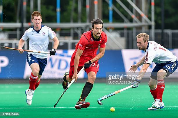 Belgium's Simon Gougnard and Britain's Barry Middleton vie for the ball during the Group B field hockey match between Belgium and Britain in the...