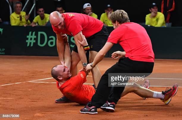 Belgium's Steve Darcis captain Johan Van Herck and David Goffin celebrate after Darcis defeated Australia's Jordan Thomson during the Davis Cup...