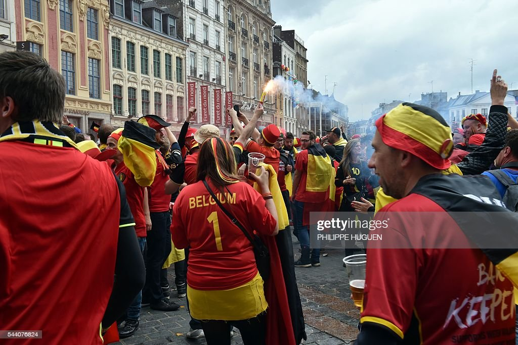 A Belgium's supporter drink beer as she gathers with other supporters in the main square, La Grand Place, in Lille on July 1, 2016 ahead of the Euro 2016 football tournament quarter final match between Belgium and Wales. / AFP / PHILIPPE