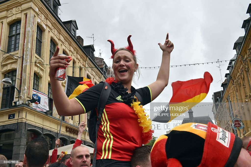 A Belgium's supporter wearing devil's horns celebrates as she gathers with other supporters in the main square, La Grand Place, in Lille on July 1, 2016 ahead of the Euro 2016 football tournament quarter final match between Belgium and Wales. / AFP / PHILIPPE