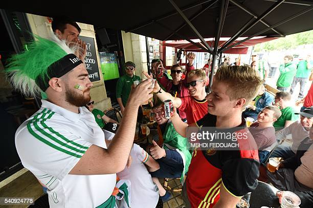 Belgium's supporters and supporters of the Republic of Ireland raise their drinks and toast as they watch the screening of the Euro 2016 group E...