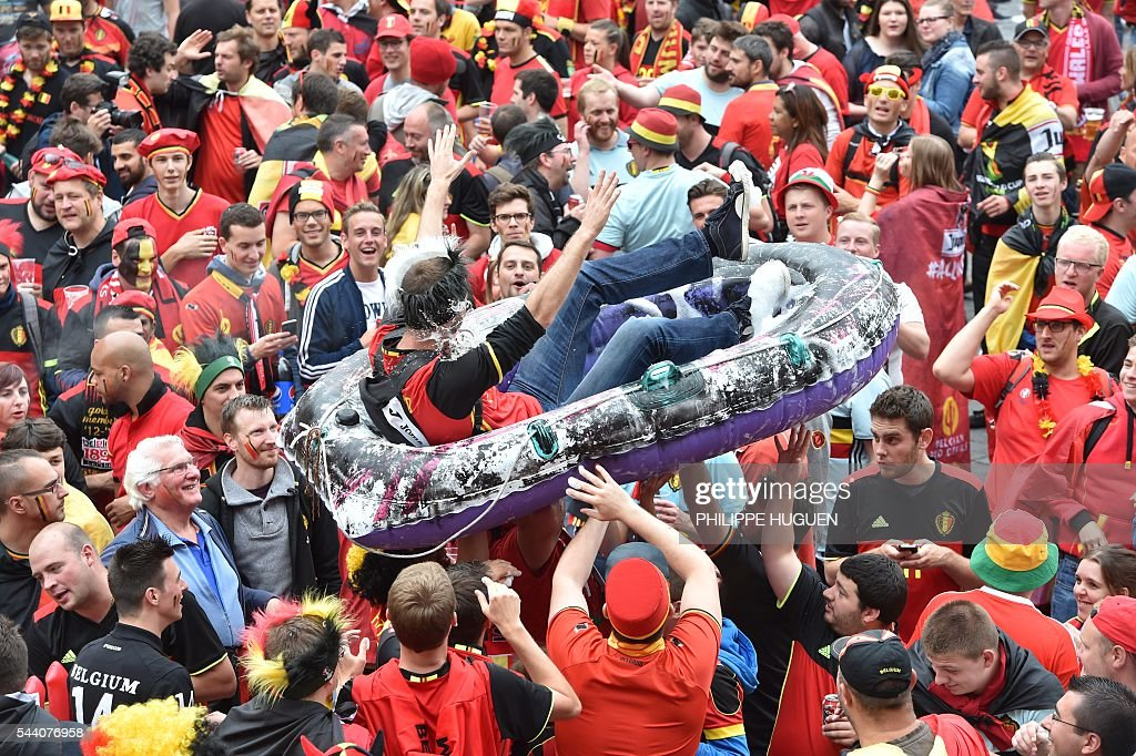 Belgium's supporters carry another one in a inflatable boat in the main square, La Grand Place, in Lille on July 1, 2016 ahead of the Euro 2016 football tournament quarter final match between Belgium and Wales. / AFP / PHILIPPE