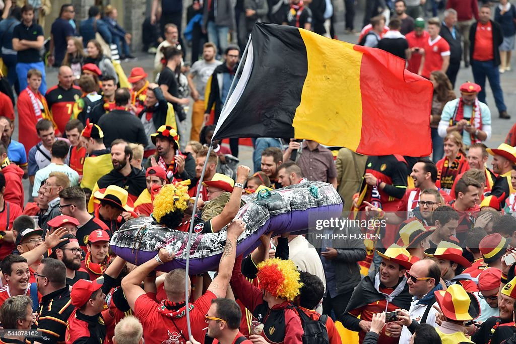 Belgium's supporters carry another one in a inflatable boat next to a Belgium's flag at the main square, La Grand Place, in Lille on July 1, 2016 ahead of the Euro 2016 football tournament quarter final match between Belgium and Wales. / AFP / PHILIPPE