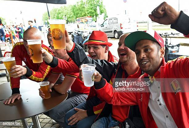 Belgium's supporters have drinks and watch the screening of the Euro 2016 group E football match between Italy and Sweden on June 17 2016 on a cafe...