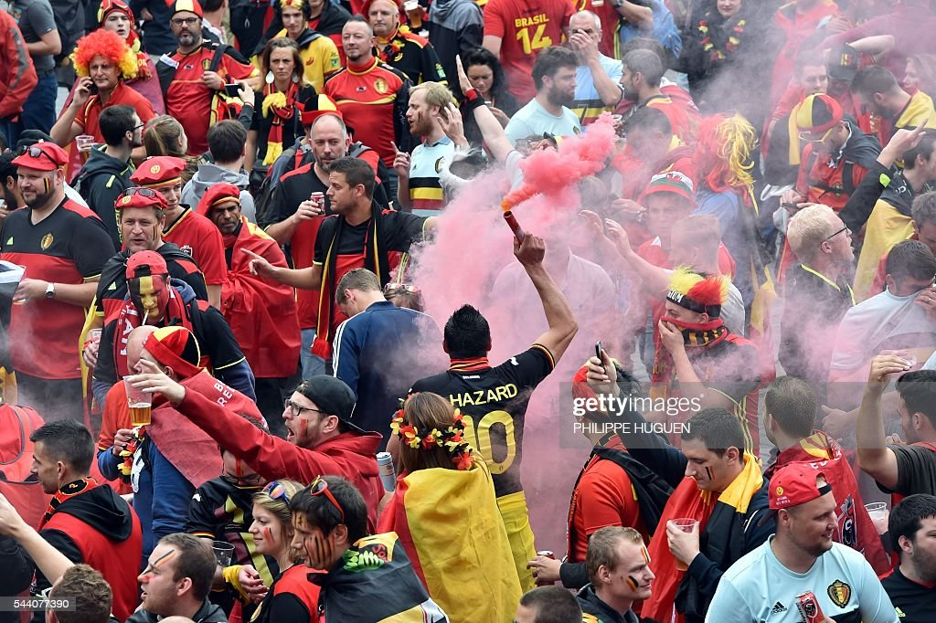 Belgium's supporters wave Belgium's cheer their team at the main square, La Grand Place, in Lille on July 1, 2016 ahead of the Euro 2016 football tournament quarter final match between Belgium and Wales. / AFP / PHILIPPE