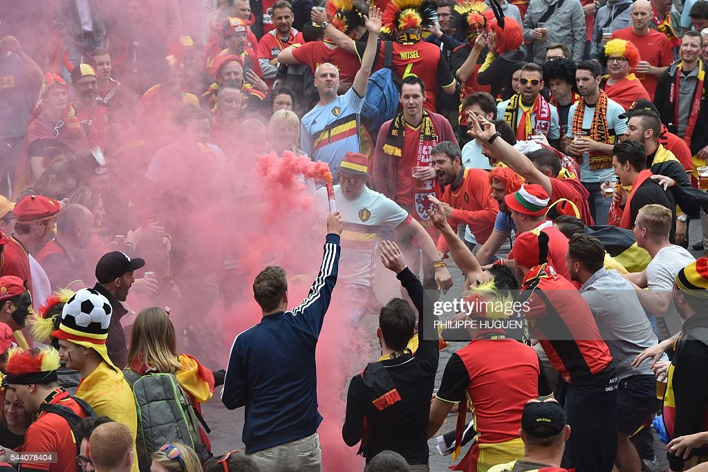 Belgium's supporters waves a torch next to other supporters at the main square, La Grand Place, in Lille on July 1, 2016 ahead of the Euro 2016 football tournament quarter final match between Belgium and Wales. / AFP / PHILIPPE