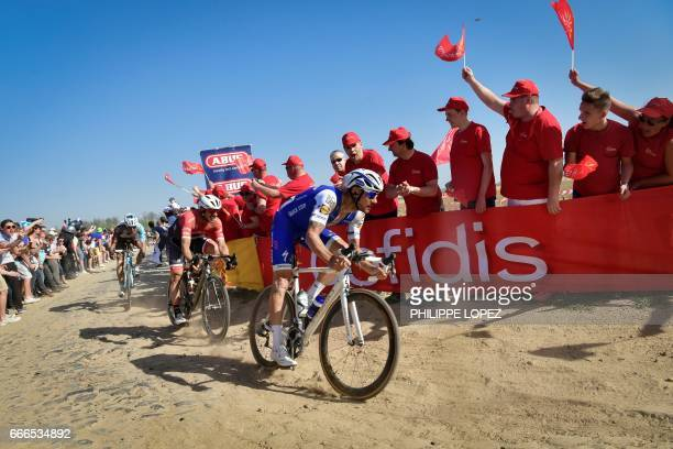 Belgium's Tom Boonen rides on the cobblestones past supporters during the 115th edition of the ParisRoubaix oneday classic cycling race between...