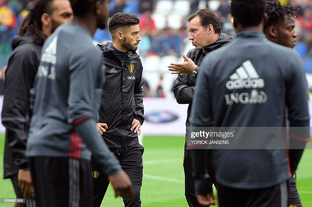 Belgium's Yannick Ferreira Carrasco (L) and Belgium's head coach Marc Wilmots (R) peak during a training session of the Belgian national football team, the Red Devils, on the first day of a training camp in Genk, on May 30, 2016, in preparation for the UEFA Euro 2016 European football championship. / AFP / BELGA / YORICK JANSENS / Belgium OUT