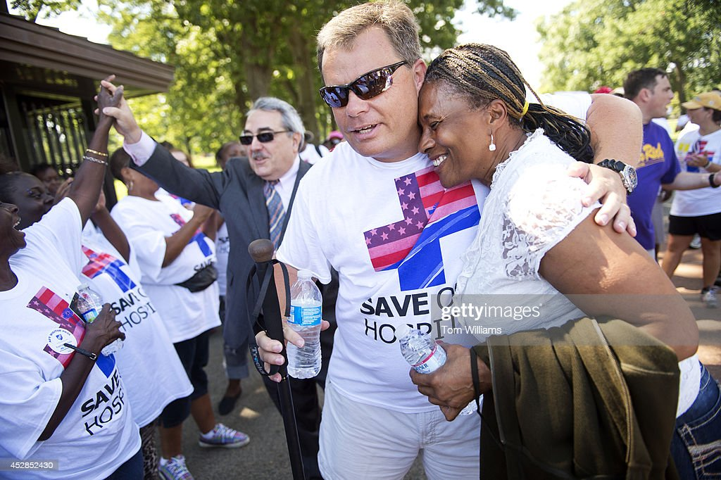 Belhaven N.C. Mayor Andy O'Neal is greeted by Lanell Cardwell in Upper Senate Park at the end of his 273-mile walk to D.C. to call attention to the closing of rural hospitals and the need for Medicaid expansion, July 28, 2014. Belhaven's Vidant Pungo Hospital was closed on July 1. Rep. G.K. Butterfield, D-N.C., appears at left.