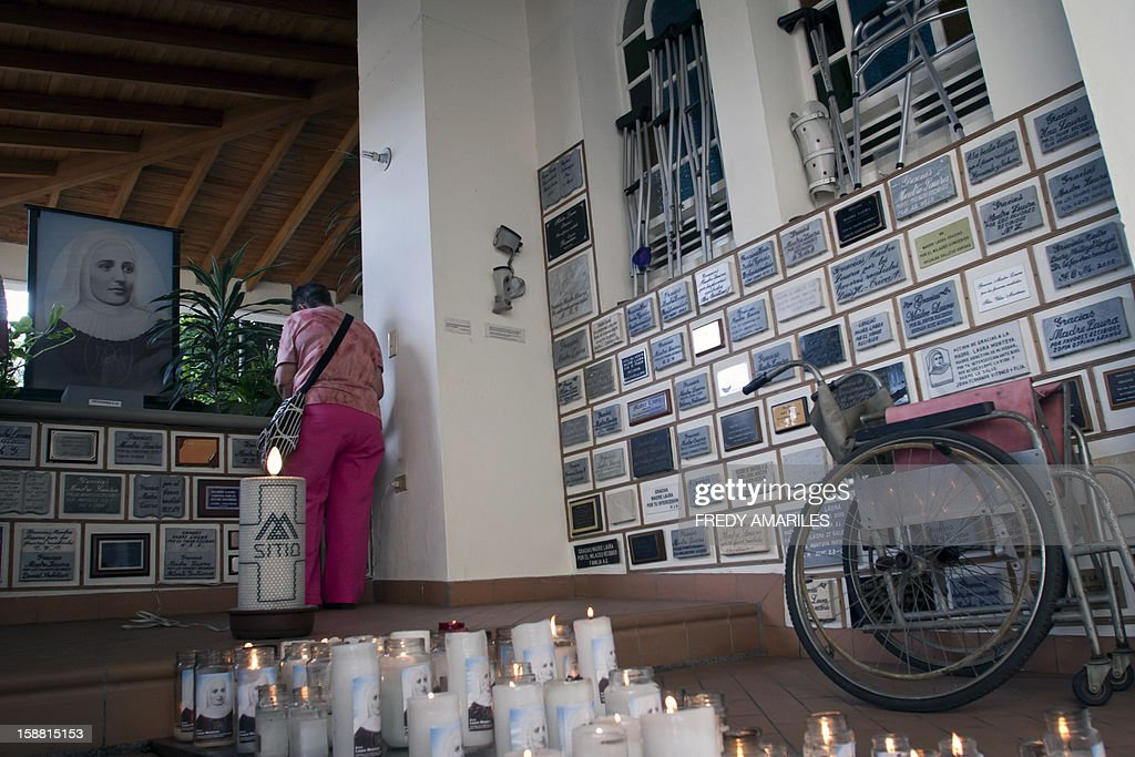 A believer stands by the picture of Mother Laura and thank you plaques at the convent where she lived in Medellin, Colombia on December 30, 2012. Mother Laura Montoya Upegui died on October 21, 1949, and was declared blessed by Pope John Paul II on April, 2004. On December 20, 2012, Pope Benedict XVI approved her canonization, making her the first Colombian saint, after recognizing a miracle. AFP PHOTO/Fredy AMARILES