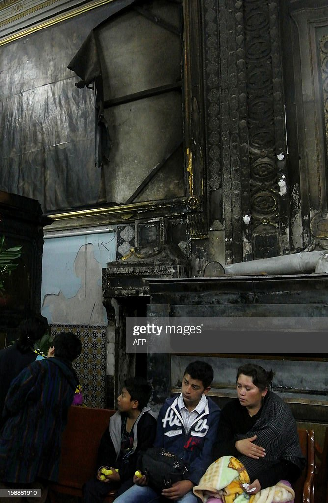 Believers are seen next to an oil painting of the XVIII century which was partially burnt by candles put by the faithful at the Santa Monica temple in Puebla, Mexico on January 01, 2013. AFP PHOTO/ Jose CASTANARES