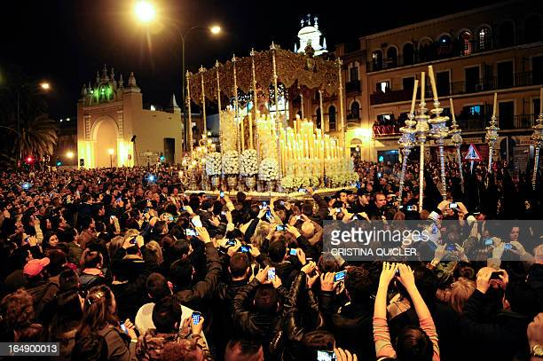 Believers gather around the Macarena Virgin during a Holy Week procession in Sevilla on March 29 2013 Christian believers around the world mark the...