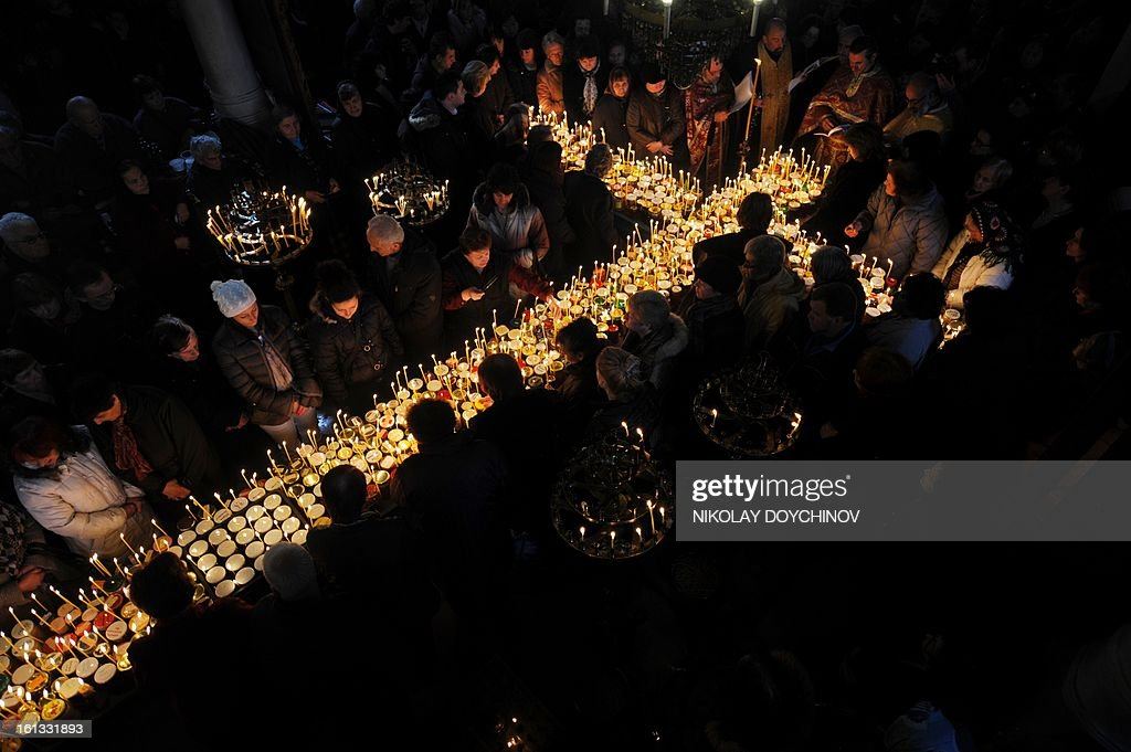 Believers pray above a cross shaped by candles placed on jars of honey in the Church of the Blessed Virgin on February 10, 2013, during a celebration in honour of St. Haralampi, protector of the beekeepers.