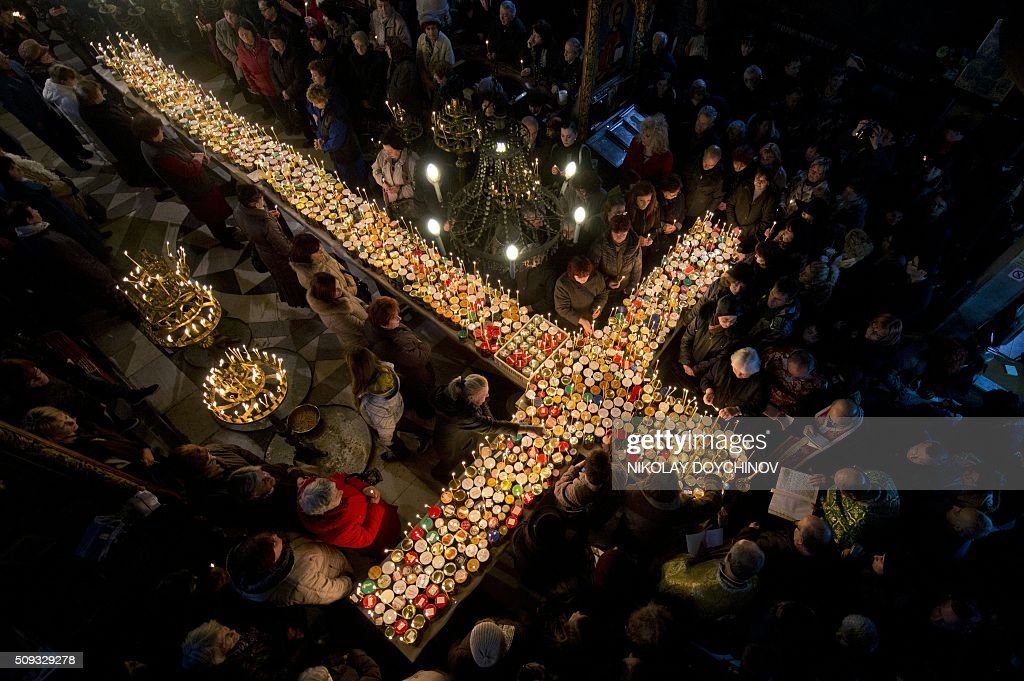 Believers pray around a cross-shaped platform covered with candles placed in jars of honey during a ceremony marking the day of Saint Haralampi, Orthodox patron saint of bee-keepers, at the Church of the Blessed Virgin in Blagoevgrad, eastern Bulgaria, on February 10, 2016. / AFP / NIKOLAY DOYCHINOV