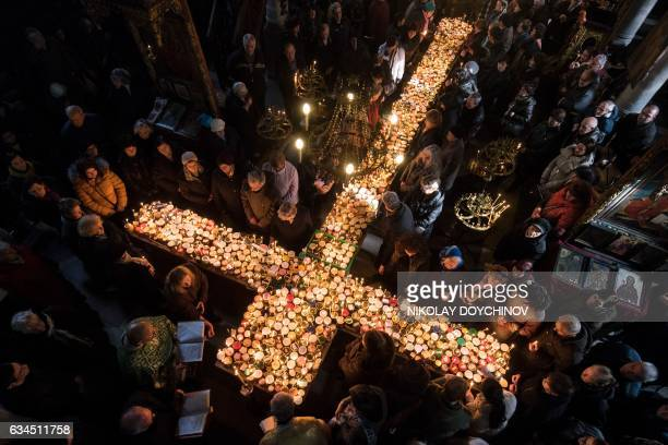 TOPSHOT Believers pray around a crossshaped platform covered with candles placed in jars of honey during a ceremony marking the day of Saint...