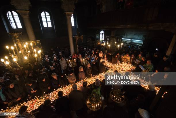 Believers pray around a crossshaped platform covered with candles placed in jars of honey during a ceremony marking the day of Saint Haralampi...