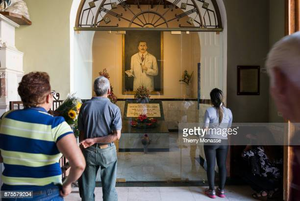 Believers stand in front of a painting of Dr Jose Gregorio Hernandez who was a Venezuelan physician in the church of Nuestra Senora de Candelaria on...
