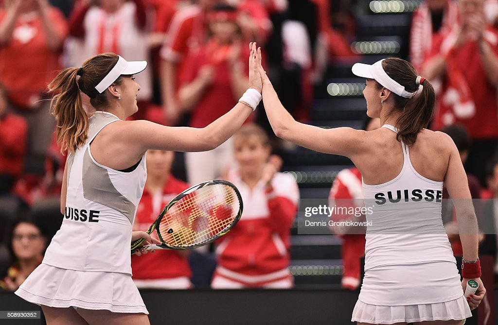 <a gi-track='captionPersonalityLinkClicked' href=/galleries/search?phrase=Belinda+Bencic&family=editorial&specificpeople=8837181 ng-click='$event.stopPropagation()'>Belinda Bencic</a> and <a gi-track='captionPersonalityLinkClicked' href=/galleries/search?phrase=Martina+Hingis&family=editorial&specificpeople=202183 ng-click='$event.stopPropagation()'>Martina Hingis</a> of Switzerland high five during thei double match against Andrea Petkovic and Anna-Lena Groenefeld of Germany on Day 2 of the 2016 FedCup World Group Round 1 match between Germany and Switzerland at Messe Leipzig on February 7, 2016 in Leipzig, Germany.