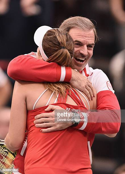 Belinda Bencic of Switzerland celebrates victory with team captain Heinz Guenthardt after her match against Angelique Kerber of Germany on Day 2 of...