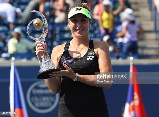 Belinda Bencic of Switzerland holds the championship trophy after defeating Simona Halep of Romania during the finals match on Day 7 of the Rogers...