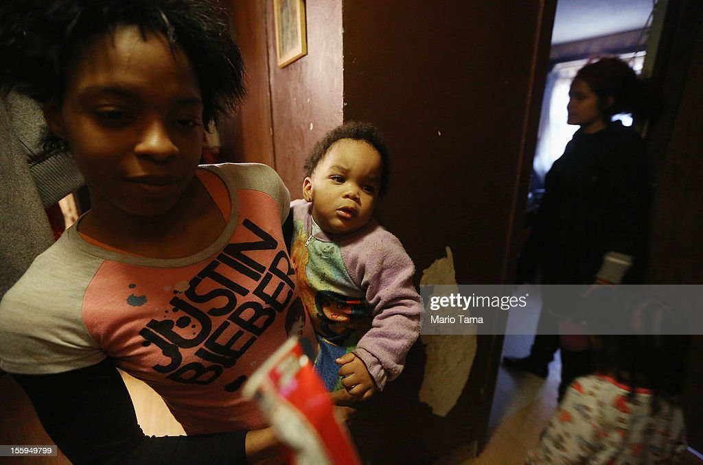 Belinda Young holds daughter Inita in their first floor apartment which flooded next to paint that peeled following storm flooding in the Ocean Bay public housing projects in the Far Rockaway neighborhood on November 9, 2012 in the Queens borough of New York City. Although the apartment now has power, some walls remain wet and paint is beginning to peel from flood damage while parents say the children have become sick. Hundreds of other Ocean Bay residents remain without heat or electricity eleven days after Superstorm Sandy struck. 53 New York City public housing buildings remain without power and 113 public housing buildings still don't have heat in the wake of the storm.