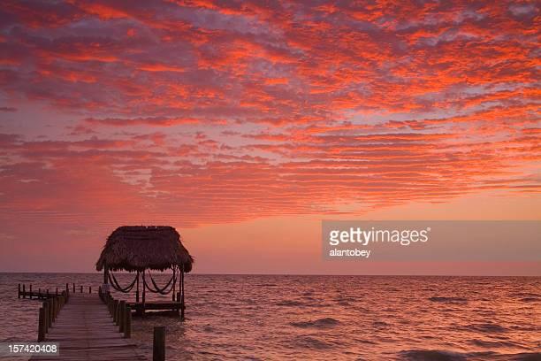 Belize: Lever du soleil sur la côte caribéenne, avec des toits de chaume et hamacs