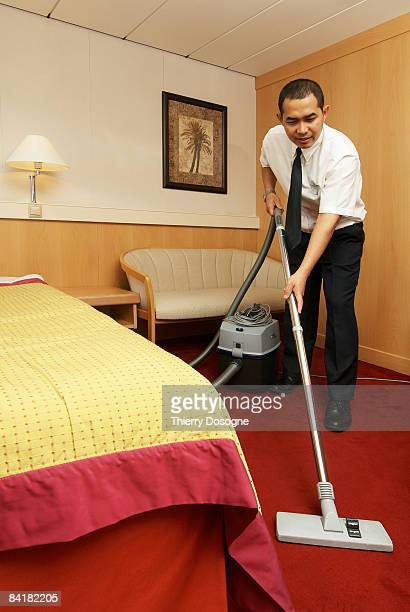 Bell boy vacuming in luxury room on cruise ship