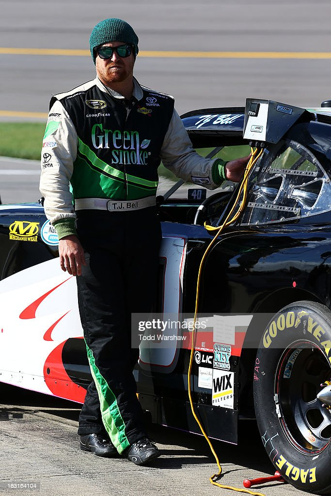 TJ Bell, driver of the #40 Curtis Key Plumbing Chevrolet, stands on the grid during qualifying for the NASCAR Nationwide Series 13th Annual Kansas Lottery 300 at Kansas Speedway on October 5, 2013 in Kansas City, Kansas.