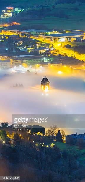 Bell tower and foggy landscape over a country