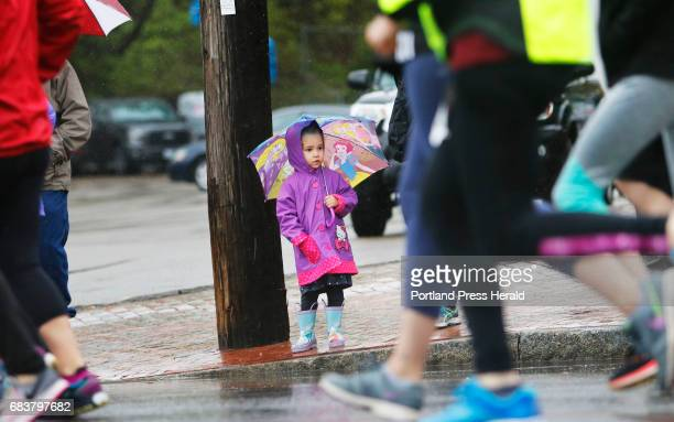 Bella Laflin of Biddeford holds a princess umbrella while watching a sea of legs pass by at the start of the Sea Dogs 5k Bella was with her mom Erin...