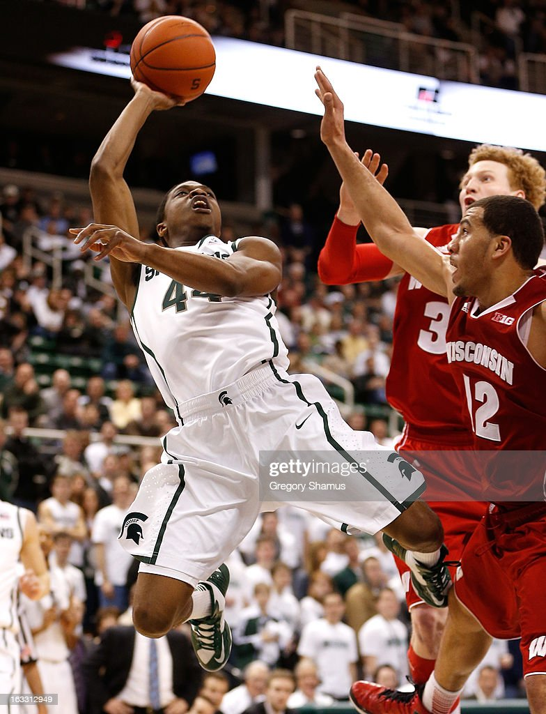 Bella Sibedwo #44 of the Michigan State Spartans tries to get a second half shot off over Traevon Jackson #12 and Mike Bruesewitz #31 of the Wisconsin Badgers at the Jack T. Breslin Student Events Center on March 7, 2013 in East Lansing, Michigan. Michigan State won the game 58-43.