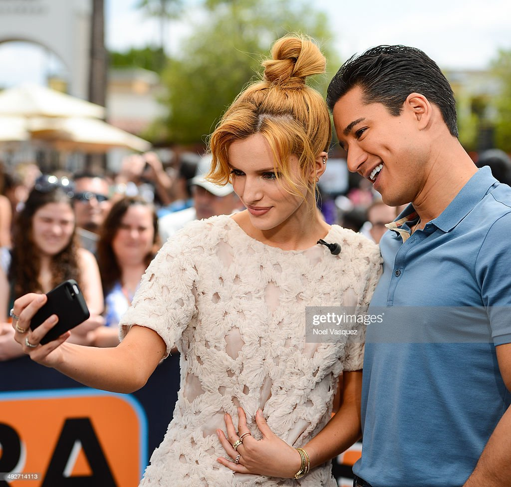 Bella Thorne (L) and Mario Lopez take a picture together at 'Extra' at Universal Studios Hollywood on May 21, 2014 in Universal City, California.