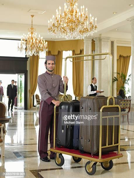 Bellboy holding luggage trolley in hotel foyer, portrait