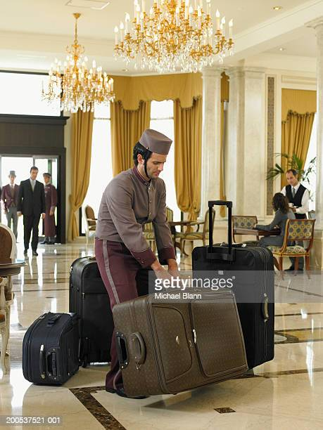 Bellboy lifting heavy suitcases in hotel foyer