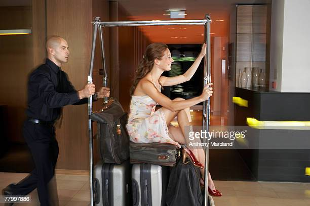 Bellboy pushing woman on luggage trolley