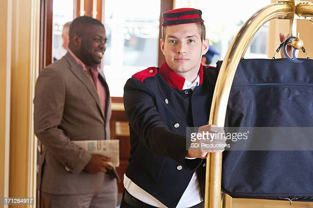 Bellhop moving luggage on cart for hotel guest