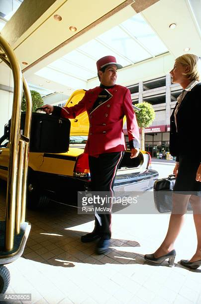 Bellhop Taking Businesswoman's Suitcases