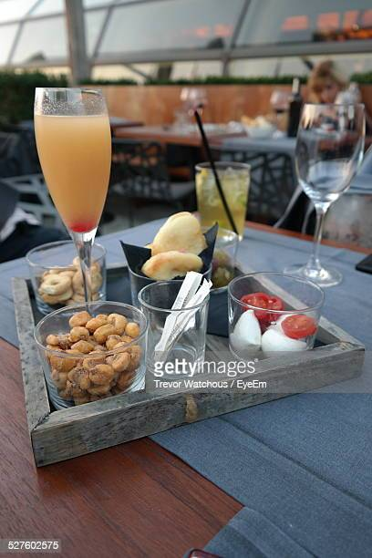 Bellini Drink Served With Snacks In Tray At Restaurant