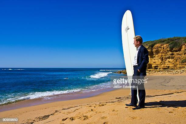 A businessman in a suit waits on the beach to go longboard surfing.