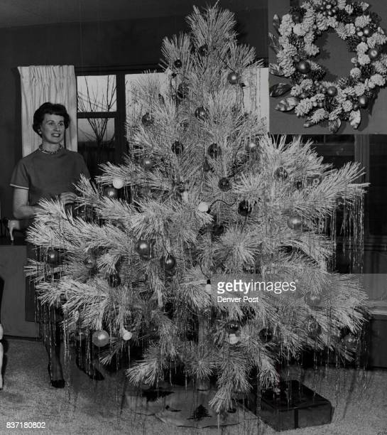 Mrs Barkley Clanahan poses by the spectacular white tree trimmed with pink aqua and purple ornaments in the living room of her contemporary hilltop...