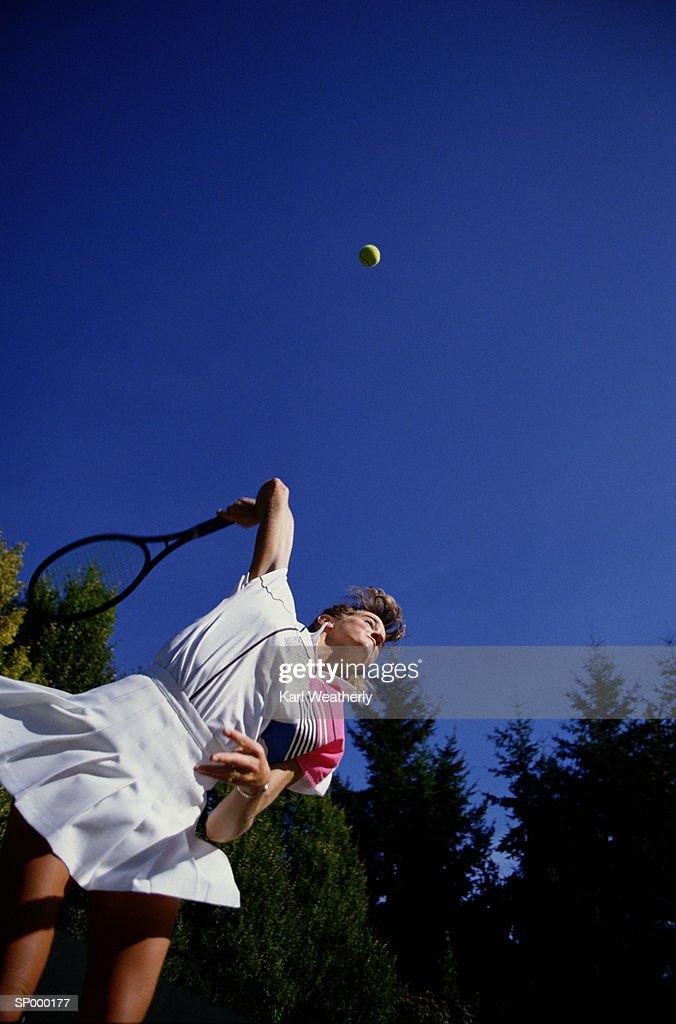 Below Shot of Woman Hitting Tennis Ball : Stock Photo